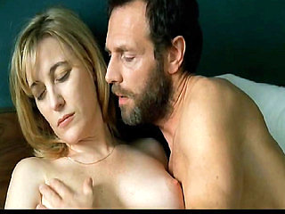 Valeria Bruni nude sitting in bed as a guy kisses her. ...